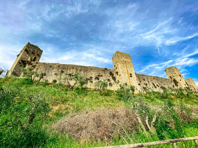 Monteriggioni la possente cinta muraria vista dalla strada bianca